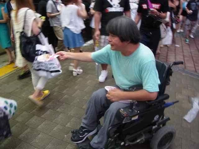 車椅子でチラシを配る男性。.jpg